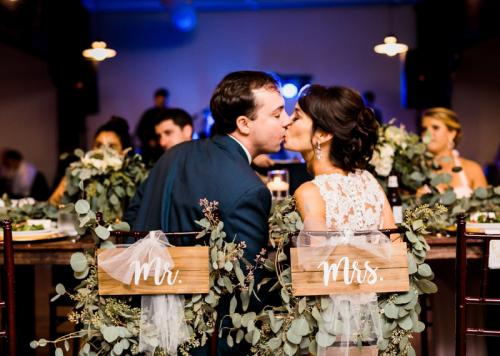 Bride-and-Groom-kiss-in-Mr-and-Mrs-chair-at-Warehouse-venue-in-downtown-Raleigh-Traine-Lindsey-Cash